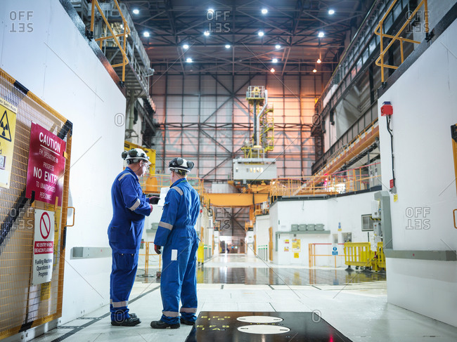 Engineers in discussion in reactor hall in nuclear power station