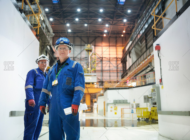 Portrait of two engineers in reactor hall in nuclear power station