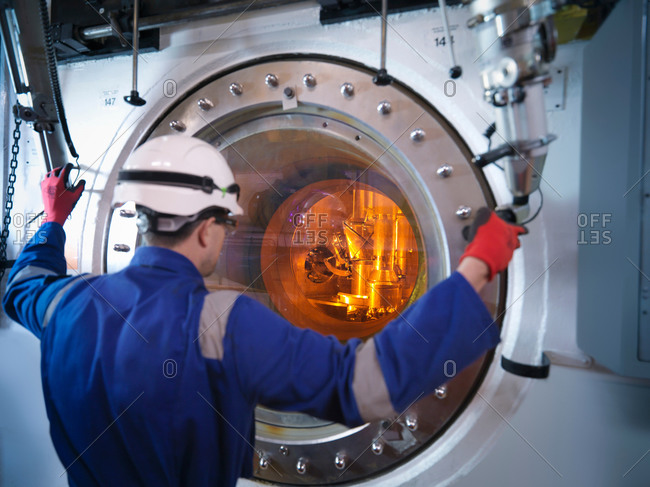 Engineer with fuel rod handling machine in nuclear power station