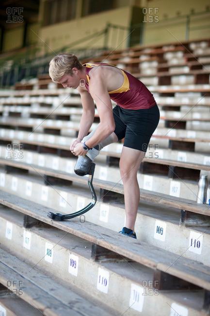 Sprinter preparing by putting on prosthetic leg