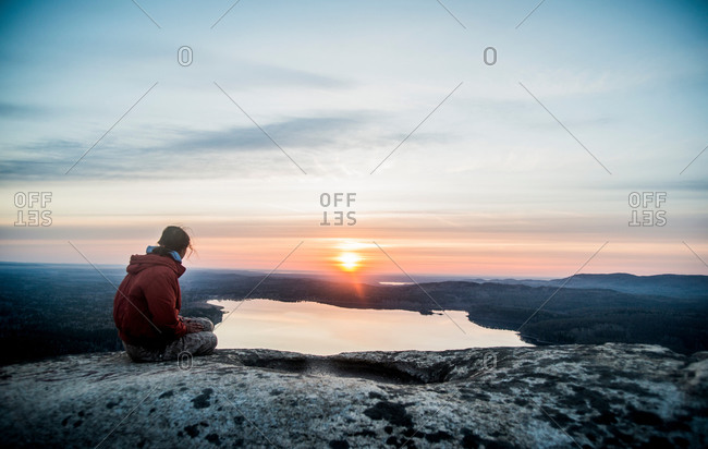 Young female hiker gazing at sunset over distant lake