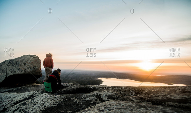 Two young female hikers gazing at sunset over distant lake