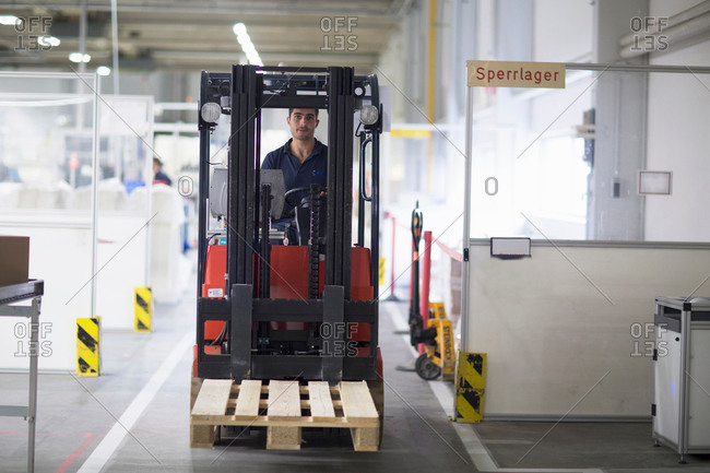 Waldkirch, Germany - July 1, 2014: Mature man using forklift truck in factory