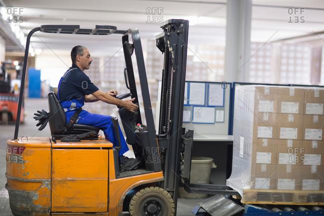 Waldkirch, Germany - July 1, 2014: Man using forklift truck in factory