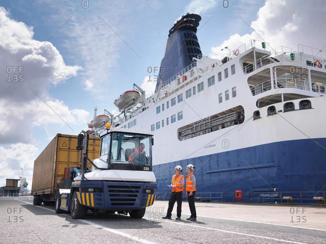 Kingston upon Hull, United Kingdom - June 26, 2014: Port workers on dock side beside ship