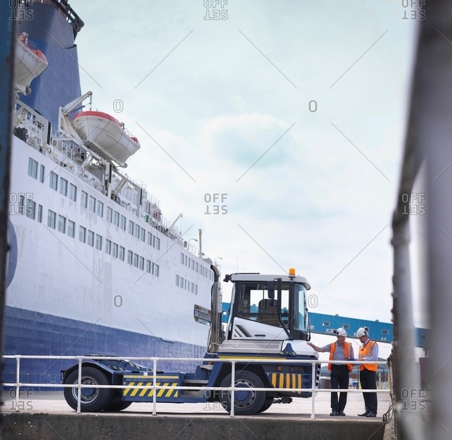 Port workers with shipping container truck and ship in port