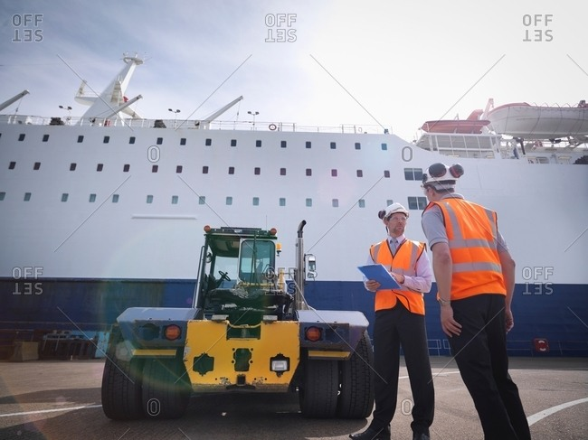 Port workers, shipping container truck and ship in port