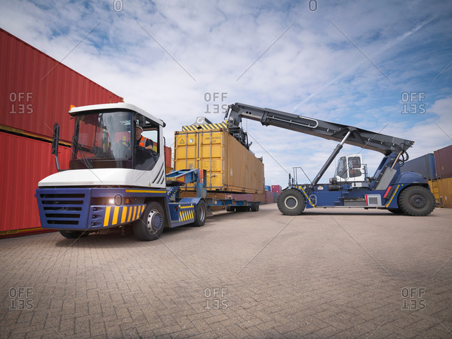 Kingston upon Hull, United Kingdom - June 26, 2014: Loading crane stacking shipping containers from truck in port