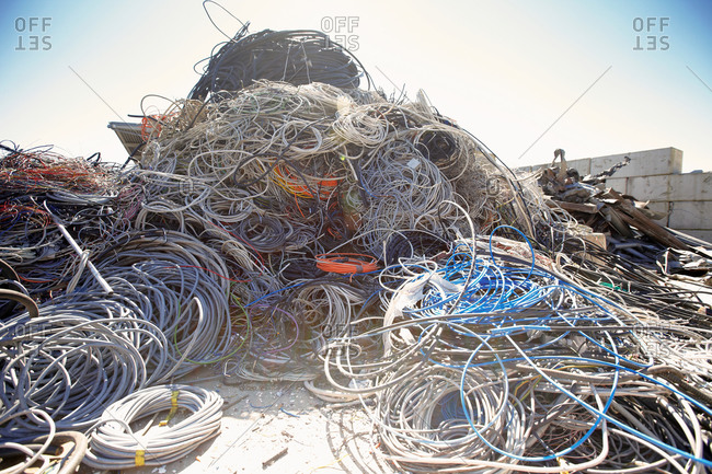 Heap of coiled and tangled cables in scrap metal yard