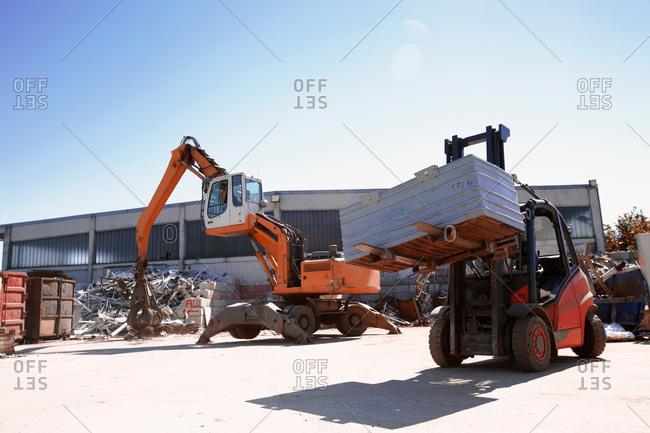 Crane grab and fork lift truck sorting and moving metals in scrap yard