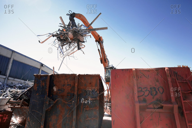 Grapple handler sorting and moving metals into scrap yard container