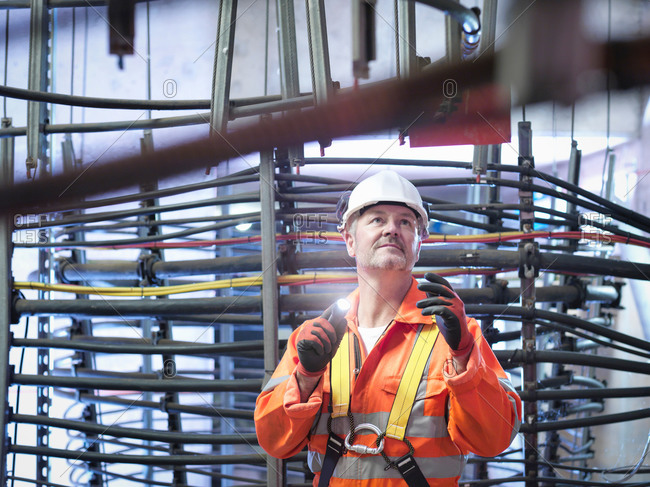Engineer inspecting cable expansion in suspension bridge