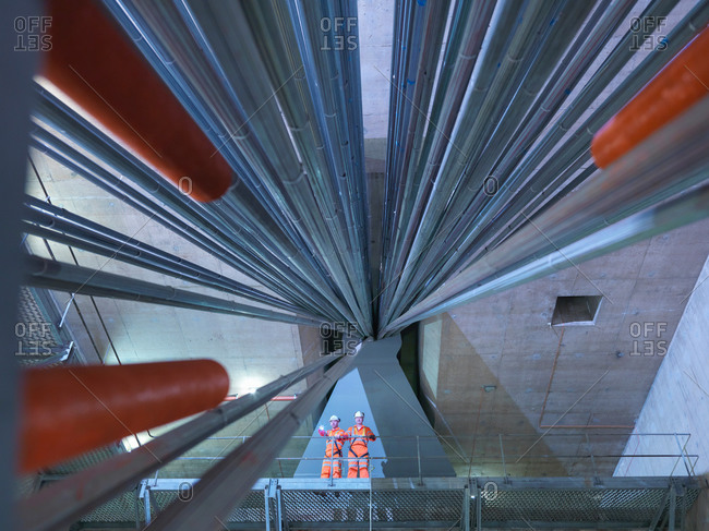 Civil engineers inspecting cable anchorage in suspension bridge, low angle view