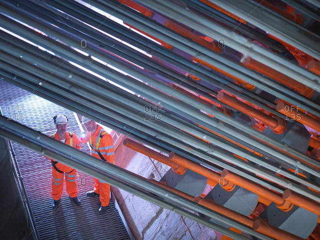 Civil engineers using torch to  inspect cable anchorage in suspension bridge