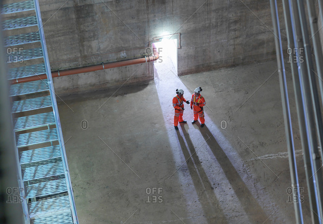 Civil engineers in discussion in suspension bridge, high angle view