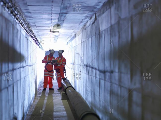Civil engineers in discussion in tunnel of suspension bridge