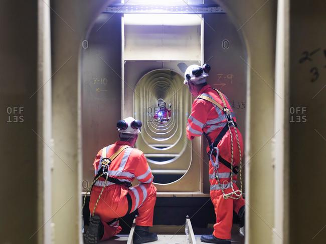 Three civil engineers inspecting structure under carriageway of suspension bridge