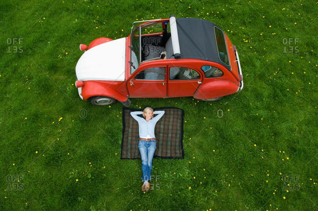 Cherington, United Kingdom - May 8, 2014: Overhead view of mature woman relaxing on picnic blanket