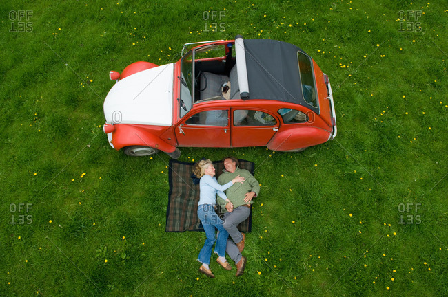 Cherington, United Kingdom - May 8, 2014: Overhead view of mature couple relaxing on picnic blanket