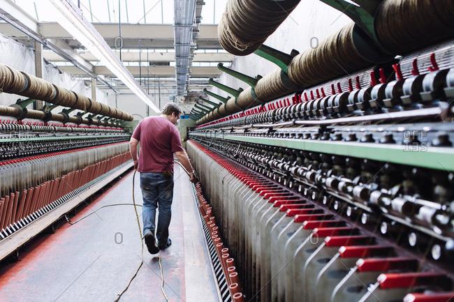 Male factory worker monitoring weaving machines in woolen mill