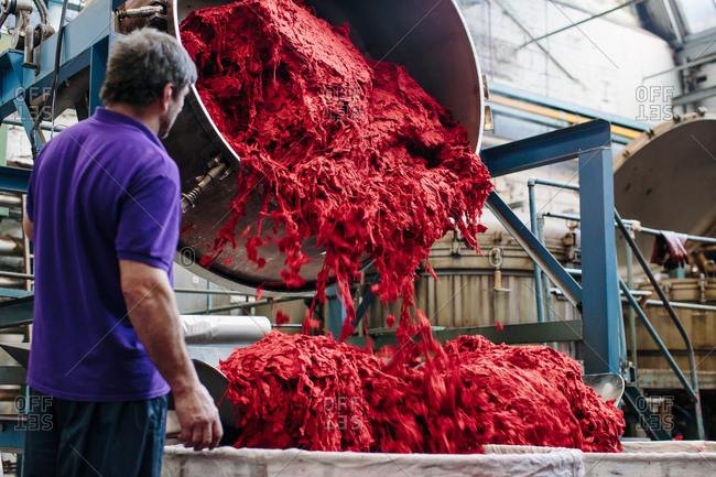 Male factory worker dyeing wool in woolen mill