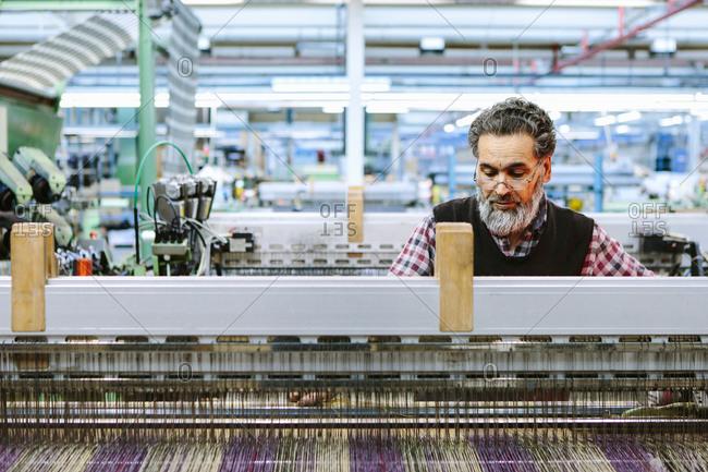 Male factory worker on weaving machine in woolen mill