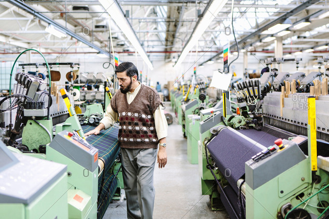 Male factory worker monitoring weaving machine quality in woolen mill