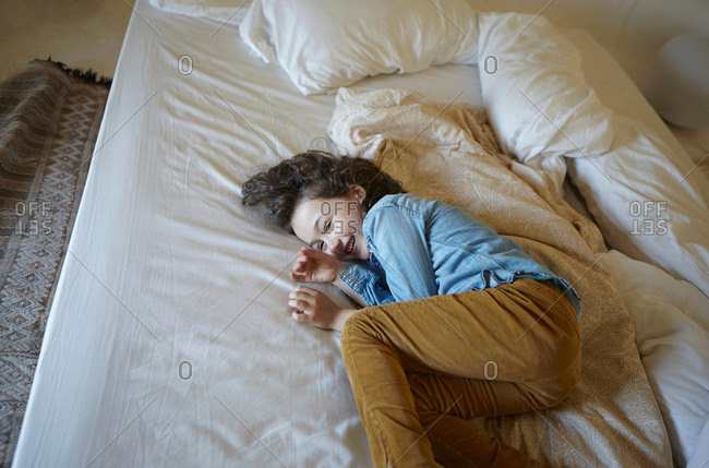 Giggling young girl curled up on bed