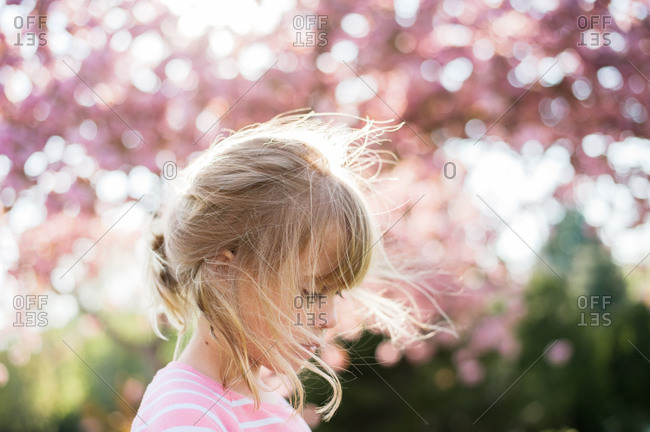 Portrait of young girl beneath cherry blossom tree