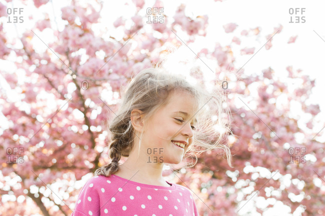 Smiling young girl beneath pink cherry blossom tree