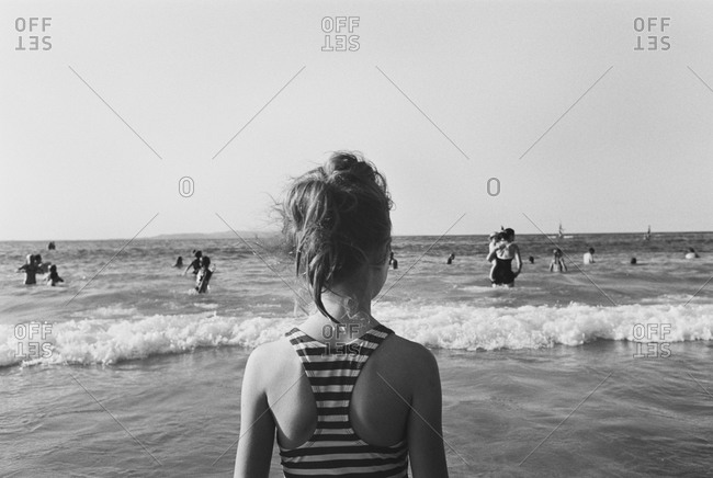 Back view of young girl watching people in the ocean