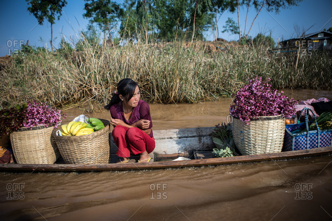 Inle Lake, Myanmar - February 2, 2015: Asian woman transporting fruit and flowers on a boat