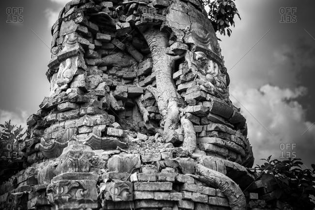 Tree growing through ruins at Shwe Indein Pagoda, Inle Lake, Myanmar