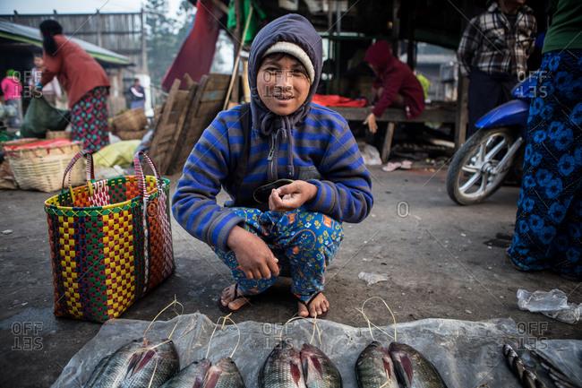 Inle Lake, Myanmar - February 3, 2015: Woman selling fish in a market