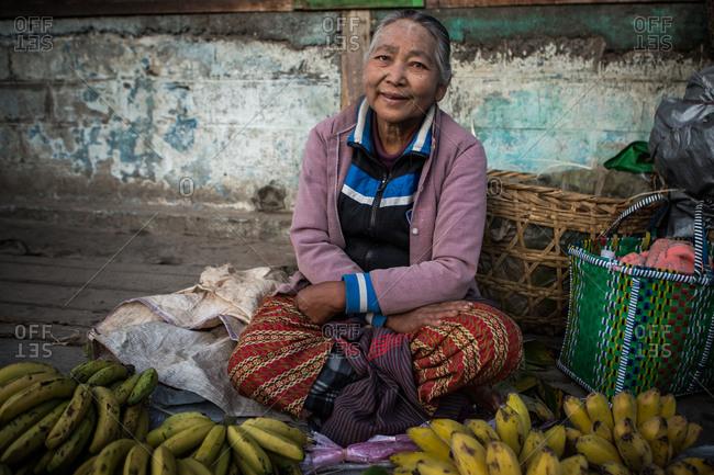 Inle Lake, Myanmar - February 3, 2015: Senior woman selling fruit in a market