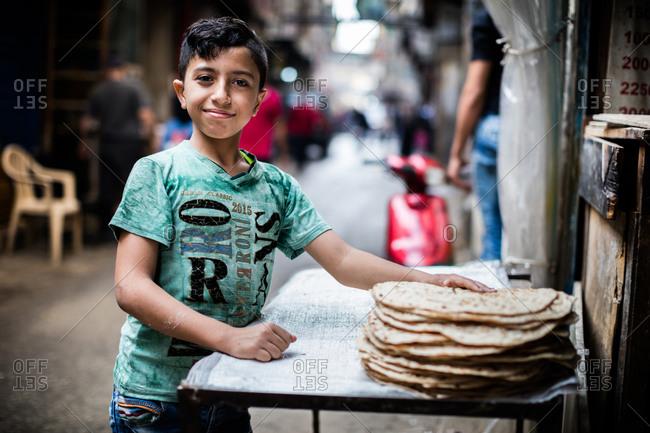 Beirut, Lebanon - November 6, 2015: Boy standing by stack of saj