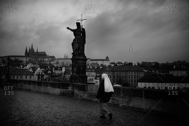 Nun walking on Charles Bridge at night, Prague, Czech Republic