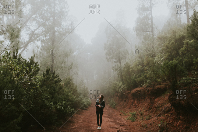 Woman standing on a path in a misty forest