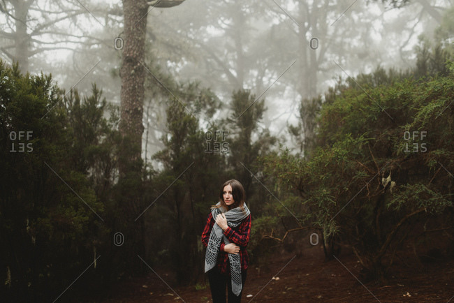 Woman standing in a misty forest