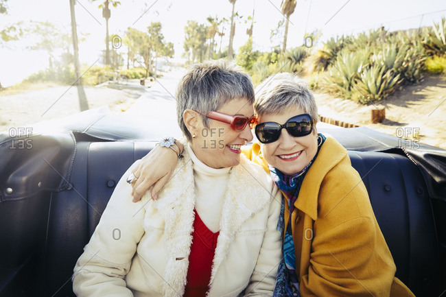 Two senior women riding in the backseat of a convertible