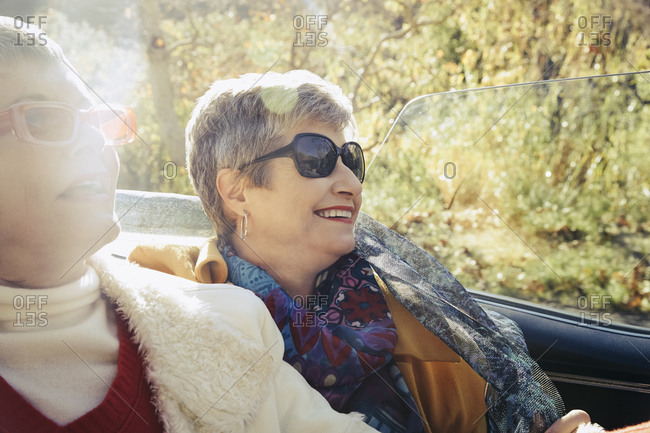Two older women riding in the backseat of a convertible