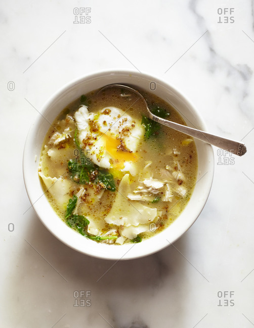 Overhead view of homemade chicken noodle soup with egg