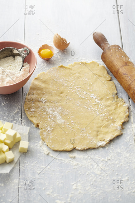 Circle of pie crust dough with rolling pin and ingredients