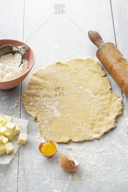 Circle of pie crust dough arranged with rolling pin and ingredients