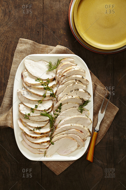 Slices of roasted turkey breast on platter with herbs