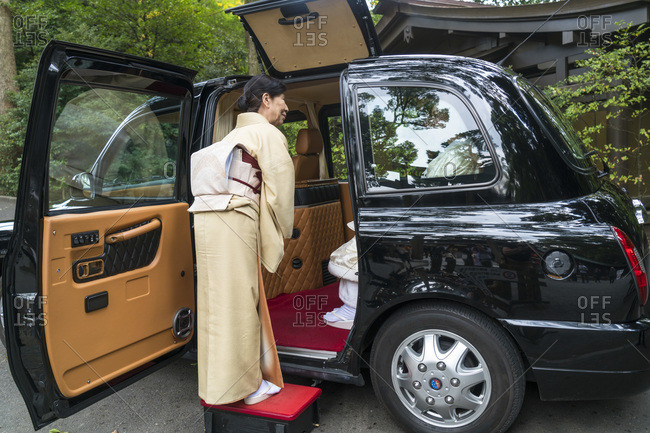 Tokyo, Japan - November 7, 2015: Woman in traditional dress escorting couple into a chauffeur-driven car in Tokyo, Japan