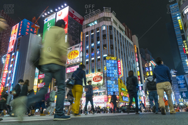Tokyo, Japan - November 7, 2015: Pedestrians crossing the street at night in the Shinjuku district, Tokyo, Japan