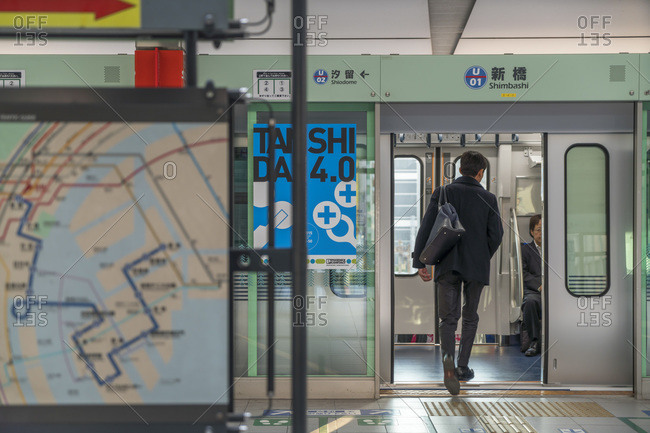 Tokyo, Japan - November 30, 2015: Man boarding a train car in the Tokyo metro station, Tokyo, Japan