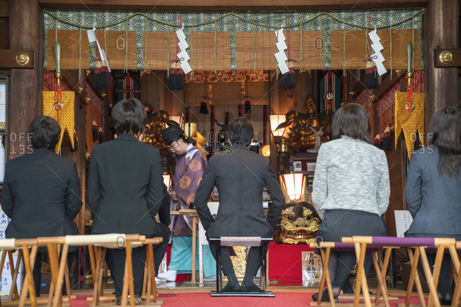 Tokyo, Japan - December 1, 2015: Business people visiting Shinto Temple before work in Tokyo, Japan