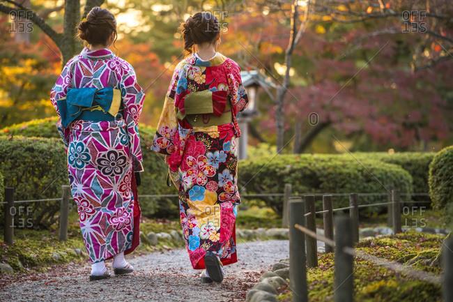 Young women in traditional Japanese dress walking in Kenrokuen Garden, Kanazawa, Japan